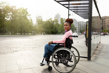 Young Black Handicapped Woman In Wheelchair Cannot Board Vehicle Suitable For Impaired Persons, Waiting On Bus Stop