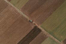 Aerial View Of Two Farm Tractors Tilling In Cultivated Fields