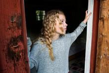 Blond Girl Passing Wooden Door