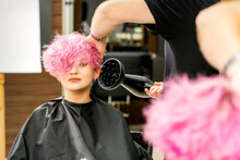 Hairdresser Drying Pink Hair Of Client