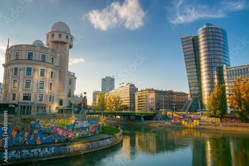 vienna, austria - OCT 17, 2019: architecture on donaukanal at sunset. water way betweein famous buildings of urania observatory and uniqa tower in evening light. popular travel destination in autumn #438108895