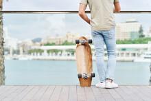 Man With Skateboard Enjoying View Of Pier