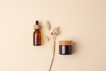Minimal Composition With Cosmetic Skin Care Products And Flowers On Pastel Beige Background. Flat Lay.