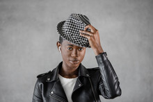 Trendy Black Model In Checkered Hat On Gray Background