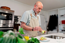 Elderly Man Extracting Avocado Pulp While Cooking At Home