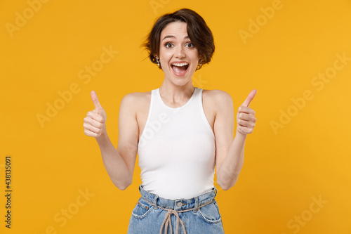 Papel de parede Young smiling happy excited caucasian woman 20s with bob haircut wearing white tank top shirt show thumbs up like gesture isolated on yellow color background studio portrait
