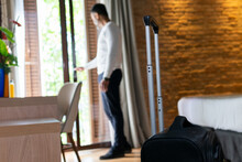 Male Tourist With Suitcase Opening Door In Hotel Room