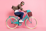 Photo of funky pretty young man wear brown shirt eyewear smiling driving cycle rucksack isolated pink color background
