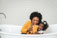 African American Family, Happy Mother And Baby Daughter Having Fun And Playing Together At The Bathroom, White Wall Backgroung