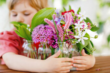 Close Up Of Little Preschool Girl With Flower Bouquet At Home. Close-up Of Toddler Child And Colorful Garden Summer Flowers In Small Bottles With Water. Closeup Of Flowers In Rainbow Colors.