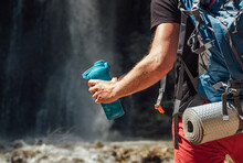 Hand Close Up With Drinking Water Bottle. Man With Backpack Dressed In Active Trekking Clothes Touristic Staying Near Mountain River Waterfall And Enjoying Nature. Traveling, Trekking Concept Image