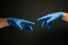 Two Hands In Medical Gloves That Reach Out To Each Other Resembling Michelangelo's Painting Of The Creation Of Adam