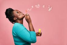 Joyful Black Woman Blowing Soap Bubbles In Studio