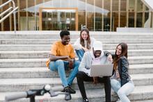 Multiethnic Students Using Laptop On Steps Of University
