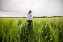 Happy Woman Walking In Green Rye Field And Enjoys Calm Nature. Freedom And Meditation Concept.