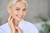 Closeup of happy smiling beautiful middle aged woman spa salon client wearing bathrobe looking at camera touching face. Spa procedures advertising. Skin care products concept. Copy space.