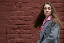 A Fashionable Girl With Hair Developing From A Sharp Turn With Her Mouth Slightly Open, Dressed In A Gray Coat And A Pink Shirt. Teenage Girl On A Background Of A Dark Brick Wall. Copy Space.