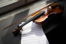 Violin Placed On Windowsill Near Sheet Music