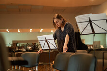Focused Woman Reading Sheet Music In Concert Hall