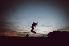Silhouette Of Woman Raising Hands And Jumping On Lawn