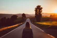 Woman Standing On Empty Road In Hilly Terrain