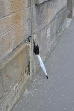 Discarded Plastic Umbrella In Leaning Against Stone Wall