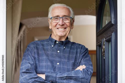 Canvastavla Portrait Of Smiling Senior Man Standing At Open Front Door Of House