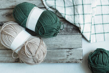Overhead View Of Balls Of Wool On A  Table Next To A Tea Towel