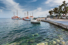 Seascape Featuring A Pier In A Mediterranean Town With Small Boats For Tourist Trips With Clear Water Near The Coast And Light Clouds On The Blue Sky