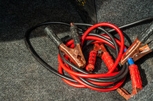 Red And Black Jumper Cables Lie In The Trunk Os A Car. Car Jumper Power Cables Red And Black Wire Cooper Clamps