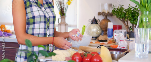 Fotografie, Obraz Brunette attractive female with curly hair in a home kitchen with a lot of flowers