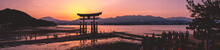 Amazing Super Wide Panorama View Of Torii Gate And Sunset With Travelers Over The Sea With Mountains In The Horizon From The Miyajima Island, Japan