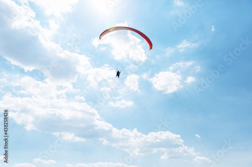 Fotografia Yellow Paraglider tandem instructor with a tourist flying into the sky with clou