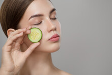 Organic Cosmetics Concept. A Young Girl With Clean Skin Holds Cucumber Slice Near Her Face. Gray Background.