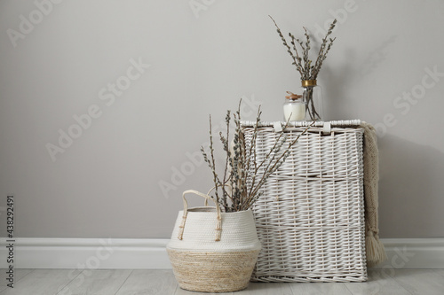Fotografie, Obraz Fresh pussy willow branches and wicker baskets indoors