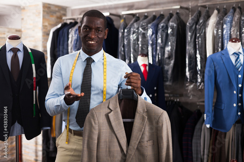 Male customer demonstrating his choice of suit in shop Fototapeta