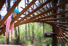 The Girl Takes A Break From The Exercises In The Rope Park.Outdoor Activities.A Child Trains In A Sports Park. Protective Helmet And Tracksuit.Sports Obstacles Consisting Of Wooden Elements And Ropes.