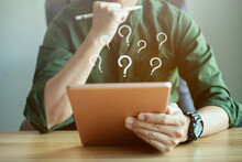 Businessman Search Information On Internet, Many Question Mark On Tablet, FAQ Concept, What Where When Why And How.