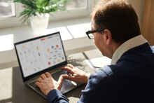 Mature Man Working On Laptop. Adult Office Worker Sitting At Table, Looking At Computer Screen, Preparing Business Presentation, Making Infographic Slides. Back View, Over Shoulder, Blurred Copy Space