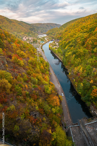 view from tarnita dam on the warm somes river. autumnal countryside landscape at sunset. trees in colorful foliage on the hill. apuseni mountains, cluj country, romania #438363234