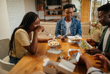 Four Black Friends Having Take Out Food At Home Together