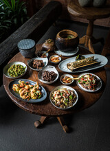 Tasty Baked Coconut And Assortment Of Yummy Exotic Salads On Round And Oval Plates With Small Wooden Spoons On Table