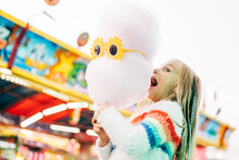 Little Girl Has Fun At The Fair With Lights And Eats Sweet Cotton.