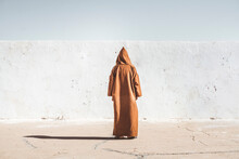 Anonymous Person In Hooded Robe Standing Near Wall