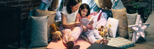 Mother And Daughter Having A Pajama Party Reading A Book In A Diy Tent