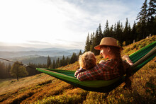 Boy Tourist Resting In A Hammock In The Mountains At Sunset