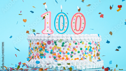 Colorful tasty birthday cake with candles shaped like the number 100. Pastel blue background. #438377890