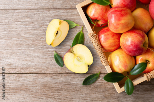 Tableau sur Toile Red apples with green leaf and half slice on wooden table background