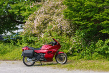A Bright Red Motorcycle Standing Against A Background Of Flowering Trees.