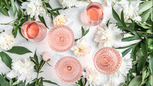 Many Glasses Of Rose Wine At Wine Tasting. Concept Of Rose Wine And Variety With Peony Flowers On White Background, Summer Drink For Party, Wine Shop Or Wine Tasting Concept